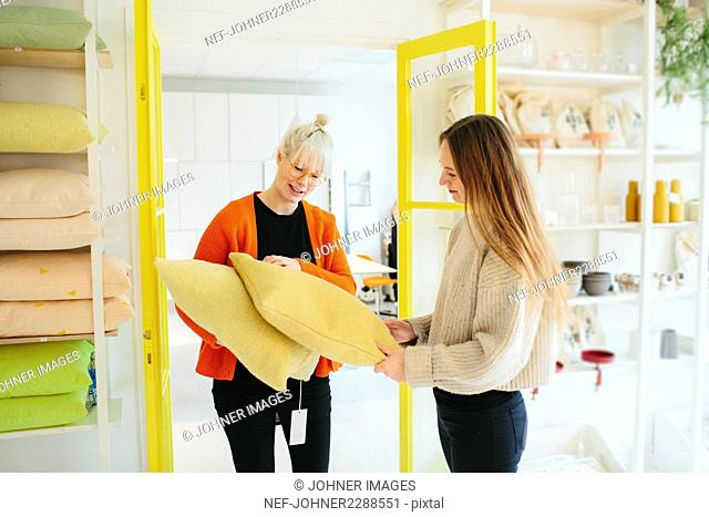 Woman in shop showing cushions to customer