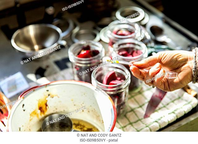 Hand of woman PH testing beetroot preserves jars in kitchen