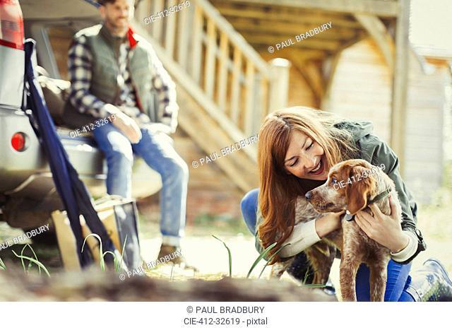 Woman petting dog outside cabin
