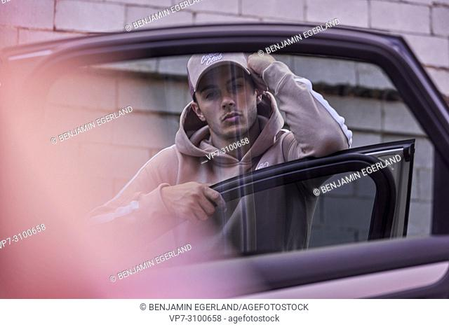 Australia, Adelaide, men's fashion blogger Reno Marrasso leaning on door of car, thoughtful, cool attitude