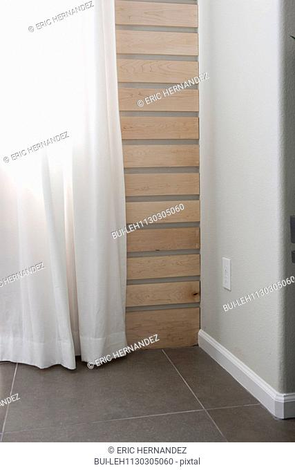 White curtain against wooden wall