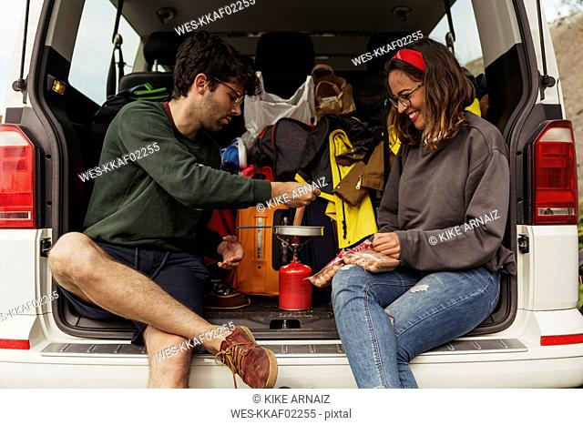 Young couple preparing sausages on a camping stove