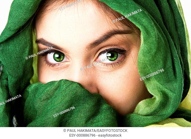 Portrait of mysterious beautiful Caucasian Hispanic Latina woman face with green penetrating eyes and green fashion scarf wrapped around head and mouth covered