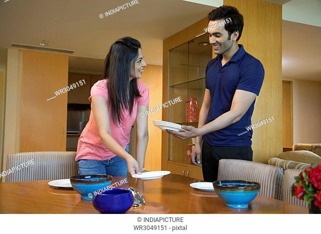 Couple setting dining table