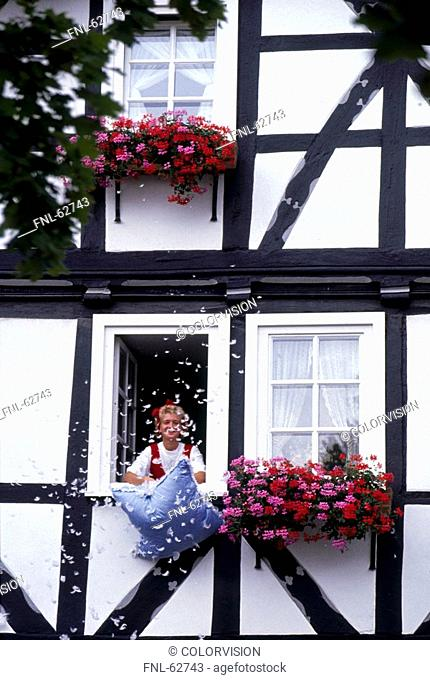 Woman with cushion at window of house, Bad Sooden-Allendorf, Germany