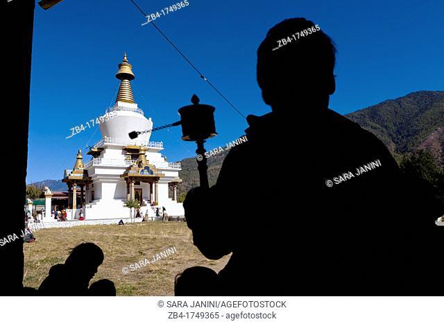 Bhutanese man holding a prayer wheel at Memorial Chorten, Thimphu, Bhutan, Asia