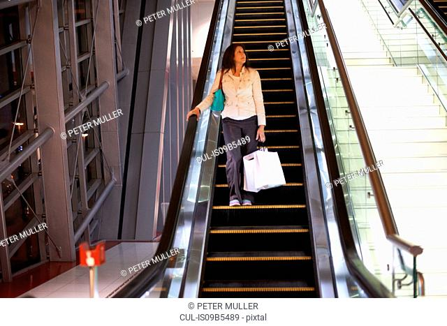 Mature woman with shopping bags moving down escalator in shopping mall, Dubai, United Arab Emirates