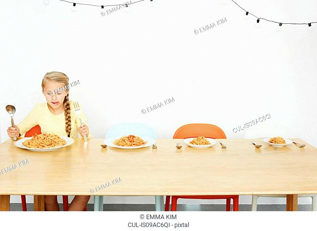 Girl sitting at table with spaghetti and three more plates