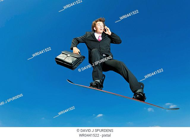 A buisnessman snowboarder on cell phone