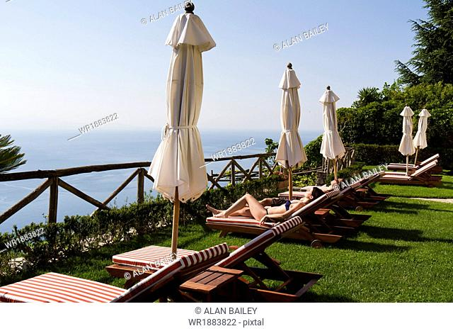 Italy, Ravello, Amalfi Coast, Couple sunbathing on deck chairs with view on sea