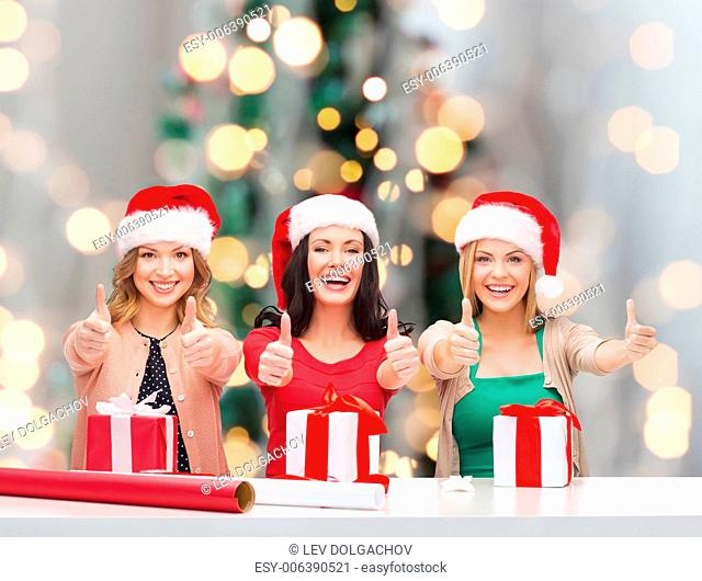 holidays, gesture, decoration and people concept - smiling women in santa helper hats with decorating paper and gift boxes showing thumbs up over christmas tree...