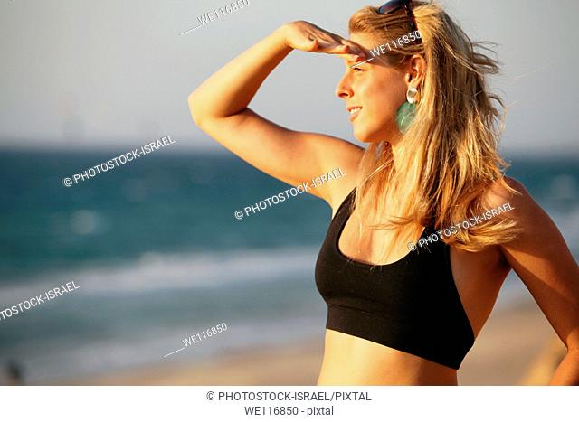 Young woman of 25 on the beach looking out to sea