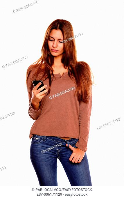 Portrait of a young woman with long brown hair sending a message with her cellphone against white background