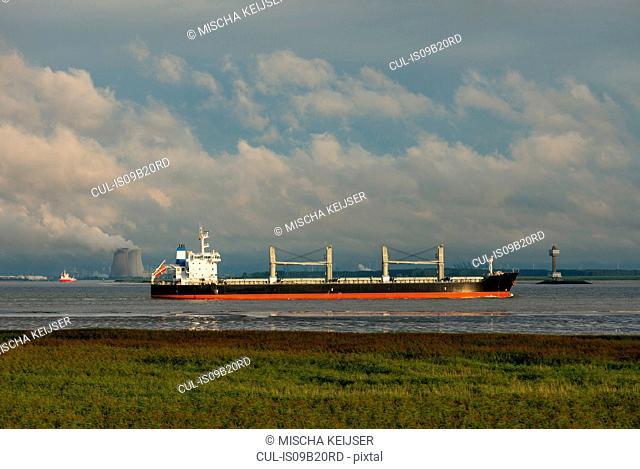 Ships sailing to and from Antwerp harbour. Nuclear power plant in the background, Rilland, Zeeland, Netherlands