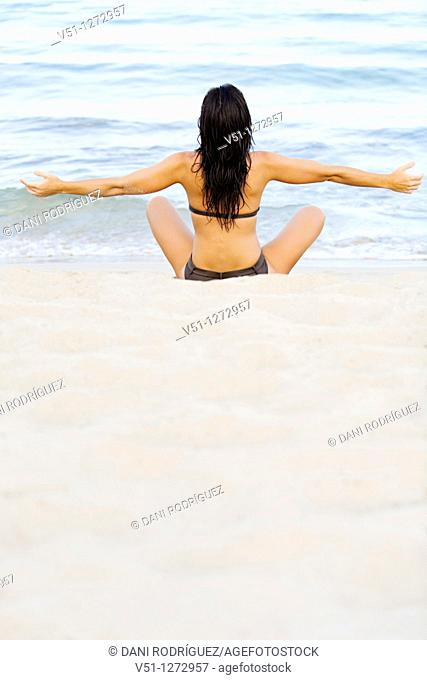 Back view of a young woman stretching at the beach