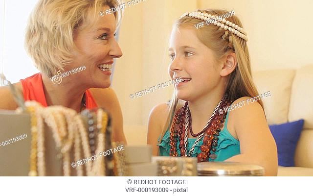 Grandmother and granddaughter playing with jewellery together indoors