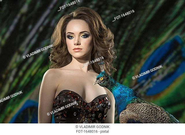 Portrait of beautiful woman by peacock against feathers