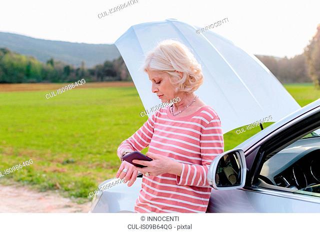 Female tourist with car breakdown waiting on rural roadside, Siena, Tuscany, Italy