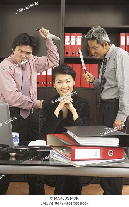 Businesswoman sitting at desk, smiling at camera, male executives behind her, holding knives