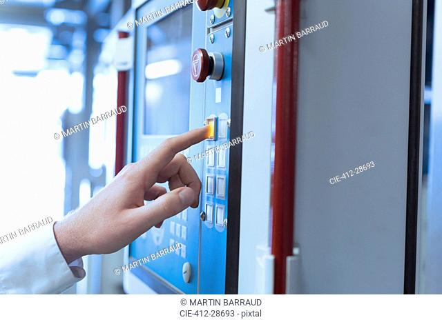 Close up of worker at control panel in factory