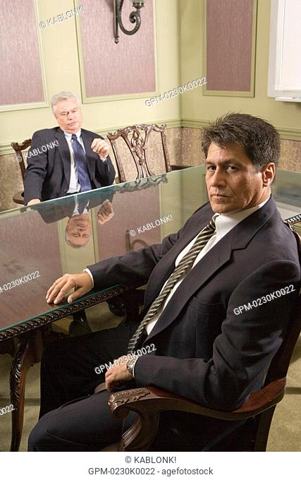 Two multi-ethnic businessmen sitting in meeting room around glass round table