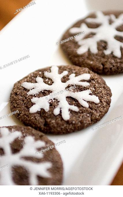 A row of decorated home baked chocolate cookies with white sugary snowflakes piped on in icing
