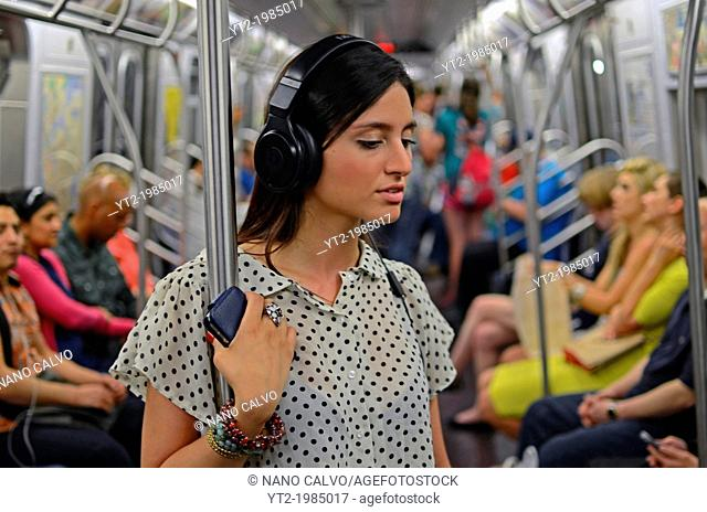 Attractive young mixed race woman traveling in subway train, New York City