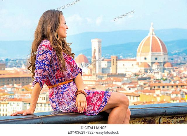 Young woman sitting against panoramic view of florence, italy and looking into distance
