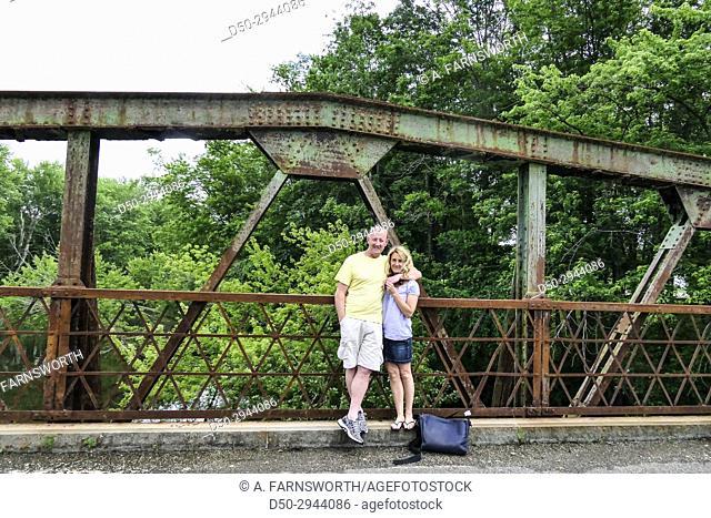 Couple on bridge, looking at camera. Great Barrington, Massachusetts, USA