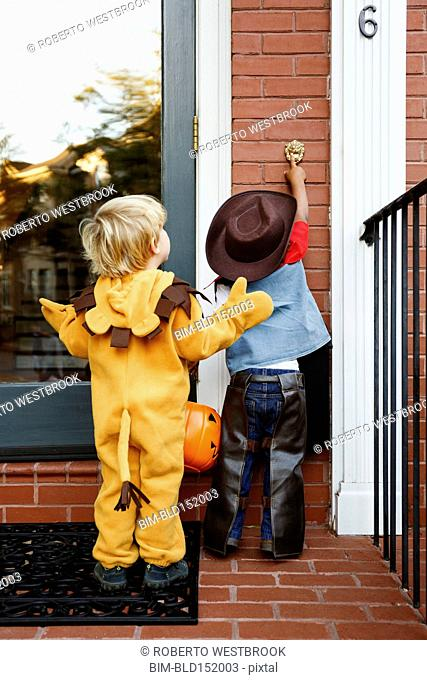 Boys in costumes trick or treating together on Halloween