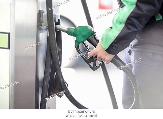 Petrol attendant holding petrol pump