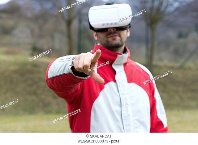 Man playing with Virtual Reality Glasses in nature