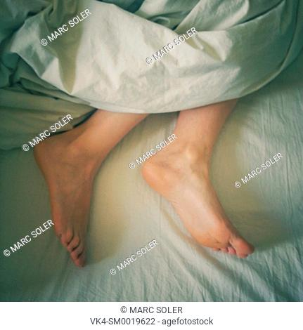 Feet of a woman under the blanket, close-up