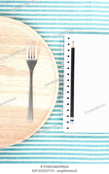 wood dish and fork put on Tablecloth at side a notebook and pencil, top view at the studio