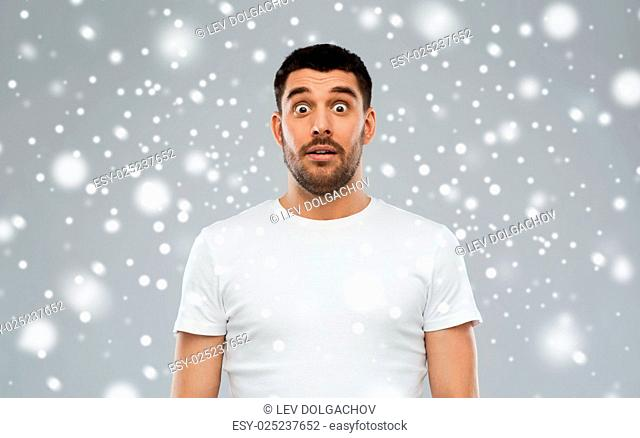 emotion, winter, christmas and people concept - scared man in white t-shirt over snow on gray background