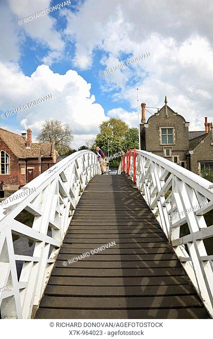 Woman standing on tip toe looking over the 'Chinese' Arched wooden Footbridge on the River Great Ouse at Godmanchester Cambridgeshire UK