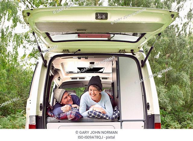 Senior couple lying inside open camper van