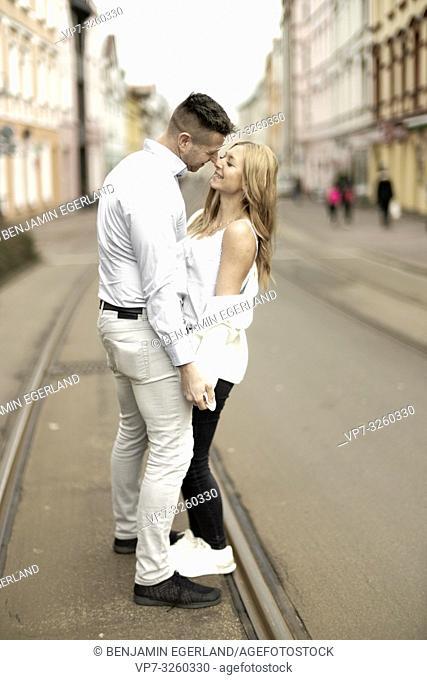 romantic couple standing on street, holding hands, in city Cottbus, Brandenburg, Germany