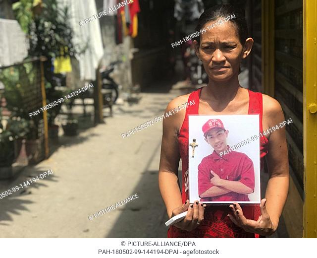19 April 2018, Philippines, Manila: The Filipino Maria Victoria Dahohoy showing a photo of her son who was shot in Bagong Silang, a suburb of the capital Manila