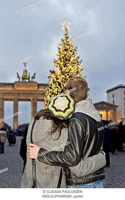 Germany, Berlin, young couple watching Brandenburg Gate and lighted Christmas tree arm in arm