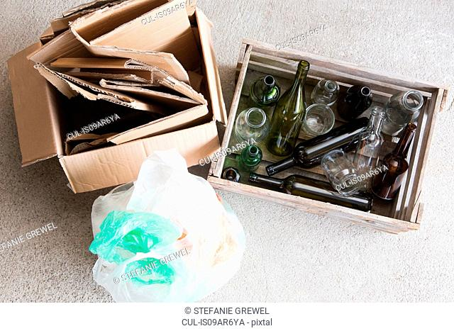 Wooden crate of empty bottles and cardboard box for recycling