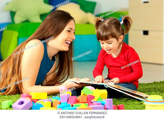 Mother and toddler playing together with a book lying on the floor in the bedroom at home with a colorful background