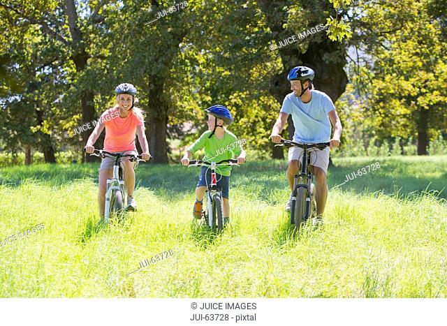 Family, mountain biking, in treelined field