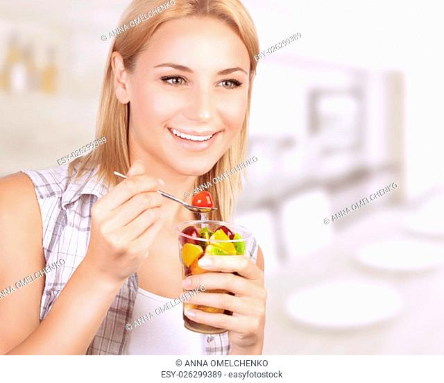 Portrait of happy woman eating tasty fruit salad at home, healthy nutrition, dieting snack, enjoying sweet organic food