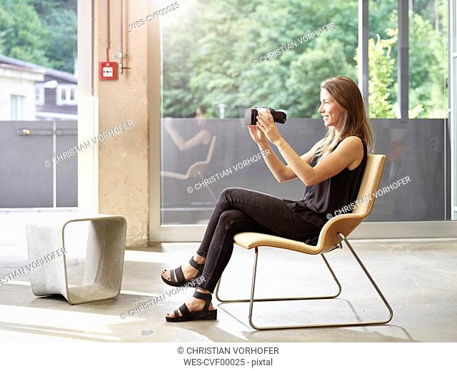 Woman holding VR glasses sitting on chair