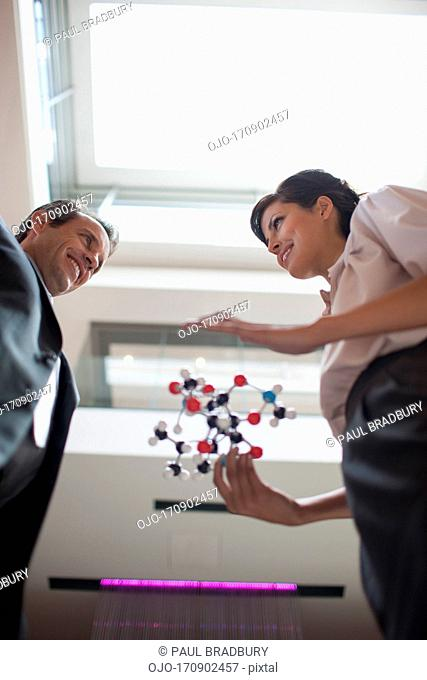 Business people holding model in office
