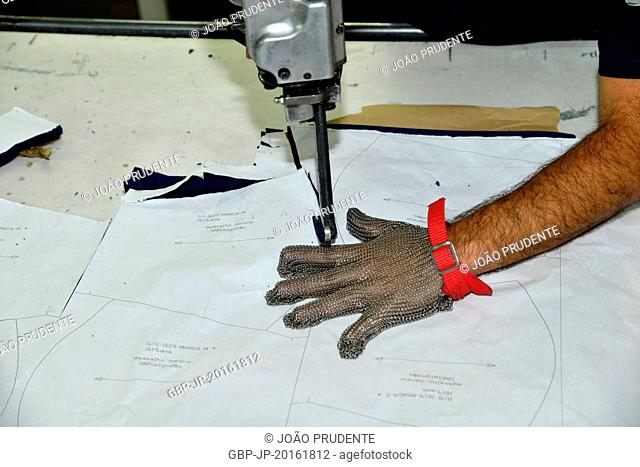 Worker with anti-cutting glove in production line of baby clothing manufacturing industry, Amparo, São Paulo, Brazil, 09.2015