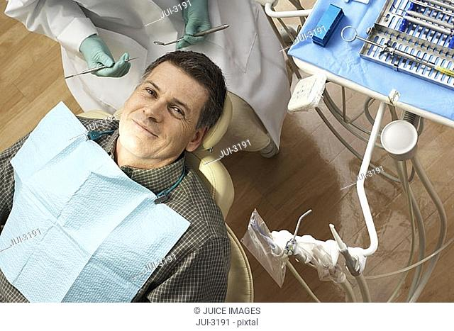 Male patient sitting in dentist's chair in dental surgery, smiling, portrait, overhead view