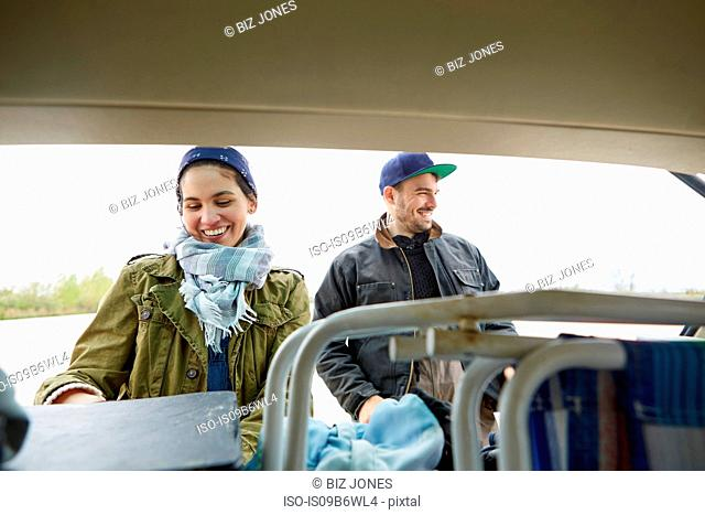 Young couple removing belongings from boot of car