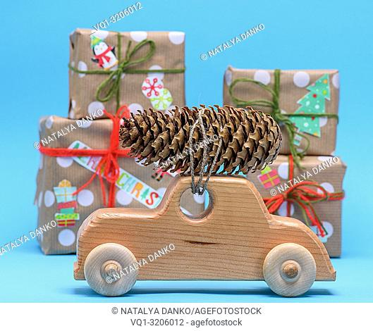 wooden machine carries a rope tied cone against a background of wrapped gifts, Christmas celebratory background